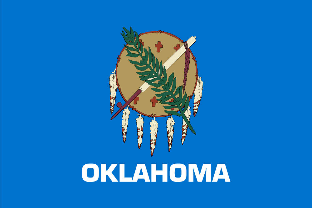 "a field of sky blue charged with an Osage war shield, a peace pipe, and an olive branch; ""Oklahoma"" is inscribed below in white"
