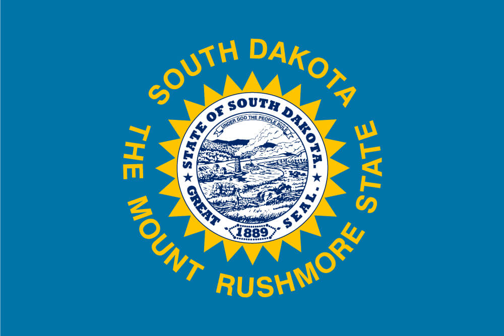 "a field of sky blue charged with the state seal in blue and white and surrounded by a serrated, golden sun and the words ""South Dakota"" and ""The Mount Rushmore State"""